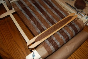 A handwoven scarf in progress on the loom.